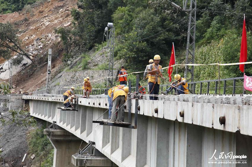 铁路抢险现场,有一群身缚安全带挂在铁路桥上昼夜坚持打孔作
