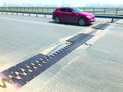 武汉通车13年的盘龙大桥无人维护 隔离护栏变形用砖垫