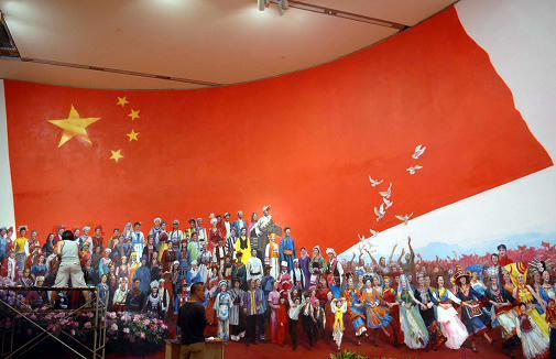 工作人员工作人员正在对一幅表现民族团结的油画进行最后的修饰.