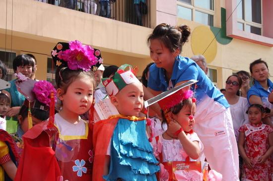 """幼儿园 银川/幼儿园老师在为孩子们上场表演""""环保时装秀""""做准备..."""